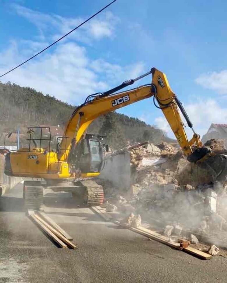 Bagr demoluje budovu